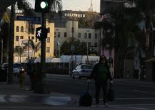 A women walks with her belongings under the Hollywood sign and across Hollywood Boulevard in Hollywood, California February 22, 2012. REUTERS/Mike Blake