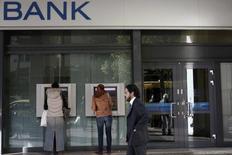 People make transactions at ATMs of an Alpha bank branch in Athens December 7, 2012. REUTERS/Yorgos Karahalis