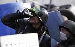 Активисты сопротивления смотрят в бинокли на баррикаде в Киеве 21 февраля 2014 года. Долларовые облигации Украины поднялись с рекордных минимумов в пятницу благодаря надеждам на разрешение политического конфликта в стране, подняв гривну к доллару. REUTERS/David Mdzinarishvili