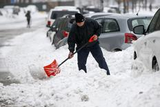 A man shovels snow in the Queens borough of New York, February 13, 2014. REUTERS/Shannon Stapleton