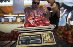 Un cliente pesa una bolsa de tomates en una feria en Sao Paulo, Brasil, mayo 4 2013. Una aguda alza estacional en los costos de la educación contribuyó a un leve aumento de la tasa de inflación de Brasil en el mes hasta mediados de febrero, dijo el viernes el estatal Instituto Brasileño de Geografía y Estadística (IBGE). REUTERS/Nacho Doce