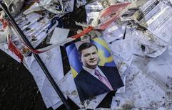 Портрет президента Украины Виктора Януковича лежит на улице в Киеве 21 февраля 2014 года. Янукович подписал с представителями оппозиции при посредничестве ЕС соглашение, призванное положить конец кровопролитному политическому кризису, унесшему более 80 жизней. REUTERS/Andrew Kravchenko