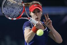 Alize Cornet of France returns the ball to Serena Williams of the U.S. during their women's singles semi-final match at the WTA Dubai Tennis Championships, February 21, 2014. REUTERS/Faisal Al Nasser