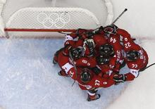 Canada's players congratulate goalie Carey Price after Canada defeated Team USA in their men's ice hockey semi-final game at the Sochi 2014 Winter Olympic Games February 21, 2014. REUTERS/Mark Blinch