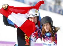 Austria's Julia Dujmovits (R), winner of the women's parallel slalom snowboard final, and her compatriot Benjamin Karl (L), who finished third in the men's competition, pose after the flower ceremonies for the parallel slalom snowboard events at the 2014 Sochi Winter Olympic Games in Rosa Khutor February 22, 2014. REUTERS/Lucas Jackson