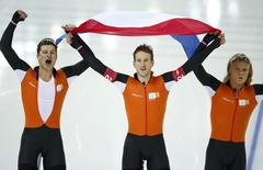 The team from the Netherlands, (L-R) Sven Kramer, Jan Blokhuijsen and Koen Verweij celebrate after competing in the men's speed skating team pursuit Gold-medal final during the 2014 Sochi Winter Olympics, February 22, 2014. REUTERS/Marko Djurica