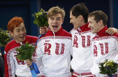 The winning Russian team celebrates on the podium during the flower ceremony for the men's 5,000 metres short track speed skating final relay race at the Iceberg Skating Palace in the Sochi 2014 Winter Olympic Games February 21, 2014. REUTERS/David Gray