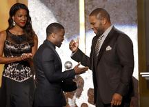 Show host Anthony Anderson presents the entertainer of the year award to actor Kevin Hart (C) during the 45th NAACP Image Awards in Pasadena, California February 22, 2014. REUTERS/Danny Moloshok