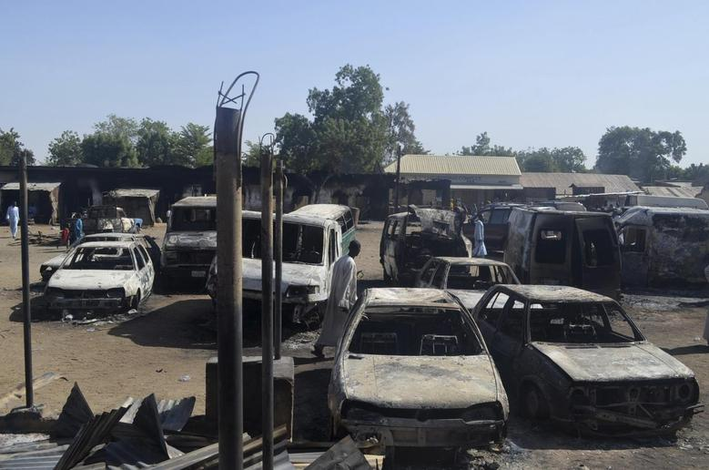 A man walks between vehicles that were destroyed during an attack by Boko Haram militants in Bama, Borno State, February 20, 2014. REUTERS/Stringer