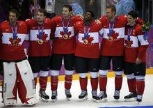 Canada's Sidney Crosby (R), Jeff Carter (2nd from R), P.K. Subban, (3rd from R) , goalie Mike Smith (L), Chris Kunitz (2nd from L) and Drew Doughty pose during the medal presentation ceremony after their team defeated Sweden in the men's ice hockey final game at the 2014 Sochi Winter Olympic Games, February 23, 2014. REUTERS/Jim Young