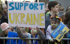 Дети держат плакаты во время акции близ украинского консульства в Нью-Йорке 23 февраля 2014 года. Оказавшаяся на грани дефолта и финансового кризиса Украина, пережившая на прошлой неделе самое масштабное в своей постсоветской истории кровопролитие и смену власти, попросила о международной финансовой помощи на сумму около $35 миллиардов в 2014-2105 годах, сообщил Минфин. REUTERS/Carlo Allegri