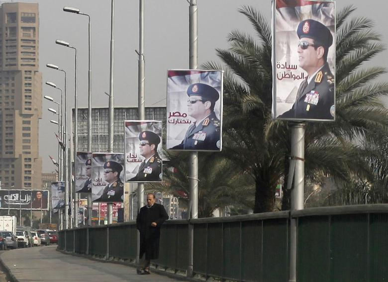 A man stands on a bridge where huge posters of Egypt's Army chief Field Marshal Abdel Fattah al-Sisi are hanged in central Cairo February 3, 2014. REUTERS/Asmaa Waguih