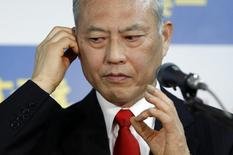 Japan's former health minister Yoichi Masuzoe checks his earphone as he prepares for an interview at his office in Tokyo February 9, 2014. REUTERS/Yuya Shino