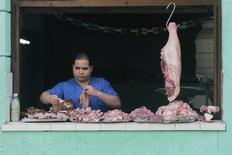 Un vendedor vende carne de puerco en una tienda callejera en La Habana, dic 27 2013. Cuba continuó reduciendo los empleos públicos y trasladando trabajadores al sector privado en el 2013, según un informe de la estatal Central de Trabajadores publicado el fin de semana, en medio de las reformas al viejo sistema de estilo soviético que impulsa el presidente Raúl Castro. REUTERS/Enrique de la Osa
