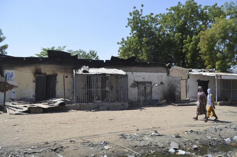 Women walk by homes destroyed by Boko Haram militants in Bama, Borno State, February 20, 2014. REUTERS/Stringer