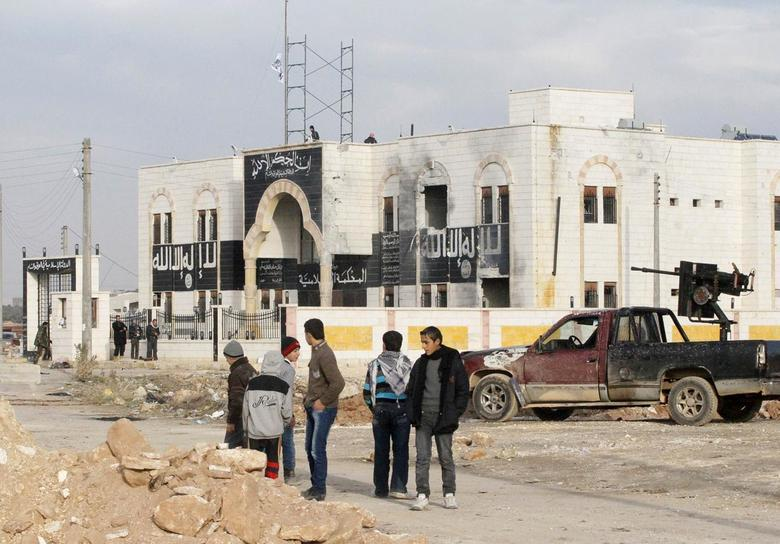 People stand in front of a former base used by fighters from the Islamic State in Iraq and the Levant (ISIL) after rebels fighters captured it from the ISIL in al-Dana town in Idlib province January 9, 2014. REUTERS/Abdalghne Karoof