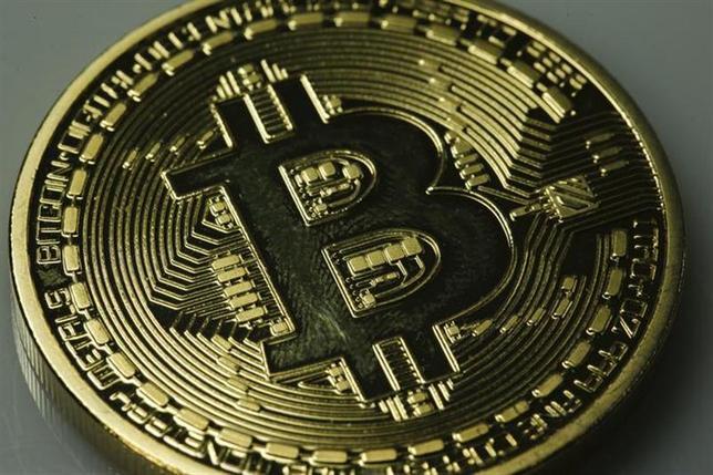 2月25日、ビットコインの大手取引所、Mt.Goxは「当面、全ての取引を停止することを決定した」とする文書をウェブサイト上に掲載した。写真は模擬ビットコイン。ベルリンで1月撮影(2014年 ロイター/Pawel Kopczynski)