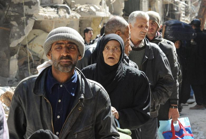 Residents wait to receive food aid distributed by U.N. Relief and Works Agency (UNRWA) at the besieged al-Yarmouk camp, south of Damascus February 24,2014, in this handout released by Syria's national news agency SANA. REUTERS/SANA/Handout via Reuters