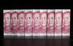 Una serie de billetes de 100 yuanes en una ilustración fotográfica realizada en Pekín, jul 11 2013. El yuan chino está ganando importancia en el mercado cambiario internacional y la moneda podría llegar a desafiar al dólar estadounidense, dijo el miércoles Yves Mersch, miembro del Consejo de Gobierno del Banco Central Europeo (BCE). REUTERS/Jason Lee