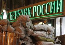 Логотип Сбербанка за баррикадой в Киеве 17 декабря 2013 года. Второй по величине российский банк ВТБ вслед за крупнейшим прекратил выдачу кредитов на Украине, где трехмесячное уличное противостояние вылилось в кровопролитие и смену власти. REUTERS/Vasily Fedosenko