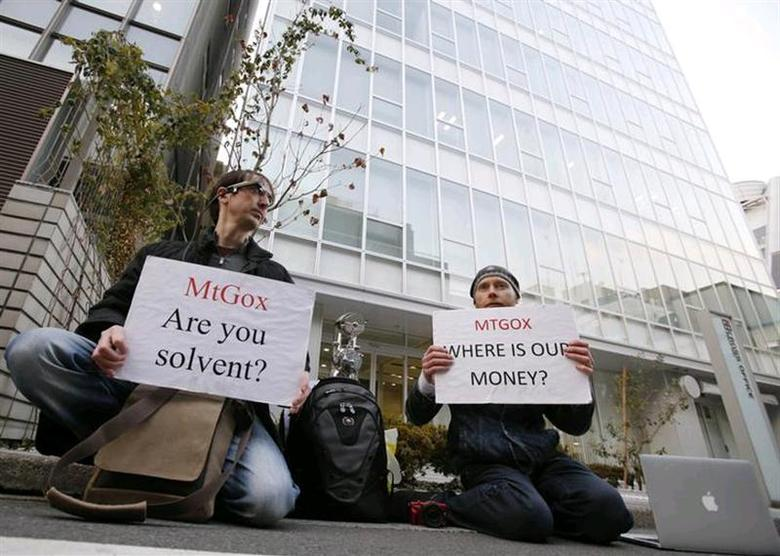 Kolin Burges (R), a self-styled cryptocurrency trader and former software engineer who came from London, and fellow protester Aaron hold placards as they demonstrate against Mt. Gox, in front of the building where the digital marketplace operator is housed in Tokyo February 25, 2014. REUTERS/Toru Hanai