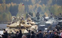 """Зрители наблюдают за движением танков Т-90МС (слева) и самоходных противотанковых пушек """"Спрут"""" на выставке вооружений Russia Arms Expo в Нижнем Тагиле 26 сентября 2013 года. Российская военная интервенция на Украину стала бы """"колоссальной ошибкой"""", предупредили США и сообщили, что рассматривают американские гарантии по кредиту на $1 миллиард и дополнительное финансирование в помощь Киеву. REUTERS/Sergei Karpukhin"""