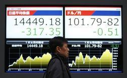Мужчина проходит мимо экрана с котировкой японского индекса Nikkei и курса иены к доллару США 20 в Токио февраля 2014 года. Азиатские фондовые рынки, кроме Японии, выросли в четверг благодаря местным новостям. REUTERS/Yuya Shino