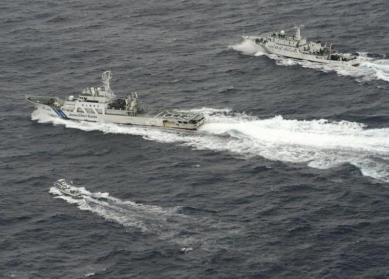 An aerial photo shows Chinese marine surveillance ship Haijian No. 66 (top) trying to approach a Japanese fishing boat (bottom) as Japan Coast Guard vessel Ishigaki cruises next to the Chinese ship, in the East China Sea, near what are known as the Senkaku isles in Japan and the Diaoyu islands in China, in this photo taken by Kyodo April 23, 2013. REUTERS/Kyodo