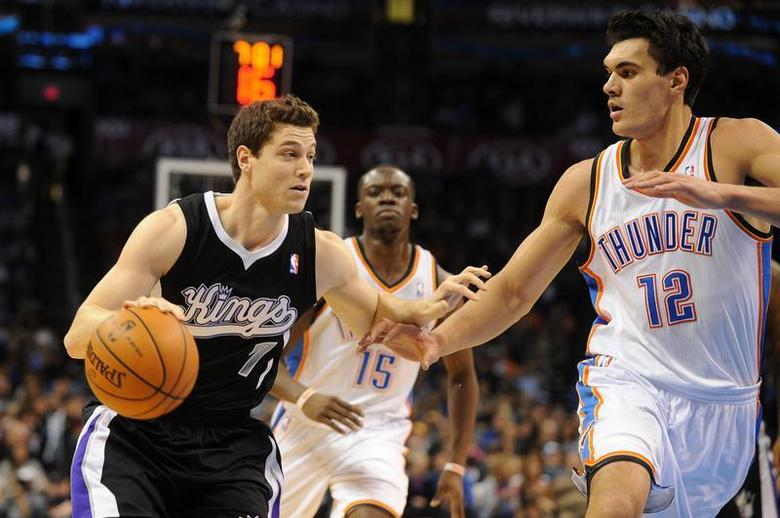 Jan 19, 2014; Oklahoma City, OK, USA; Sacramento Kings point guard Jimmer Fredette (7) dribbles the ball as Oklahoma City Thunder center Steven Adams (12) defends during the second quarter at Chesapeake Energy Arena. Mandatory Credit: Mark D. Smith-USA TODAY Sports - RTX17LYD