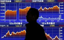 Человек проходит брокерской конторы в Токио 21 февраля 2014 года. Азиатские фондовые рынки завершили февраль разнонаправленно под воздействием локальных факторов. REUTERS/Yuya Shino