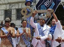 Rio de Janeiro's Mayor Eduardo Paes (R) hands over the city's ceremonial key to the Rei Momo, or Carnival King Wilson Neto (2nd R) at Cidade Palace in Rio de Janeiro February 28, 2014. REUTERS/Sergio Moraes