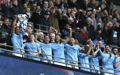 Manchester City captain Vincent Kompany holds aloft the trophy after defeating Sunderland to win the English League Cup final soccer match at Wembley Stadium in London March 2, 2014. REUTERS/Suzanne Plunkett