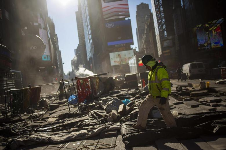 A worker walks while repairing the road at Times Square in New York December 13, 2013. REUTERS/Eric Thayer