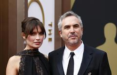 "Mexican director Alfonso Cuaron, best director nominee for his film ""Gravity,"" and his partner Sheherazade Goldsmith arrive at the 86th Academy Awards in Hollywood, California March 2, 2014. REUTERS/Lucas Jackson"