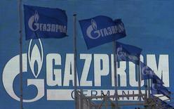 Bandeiras ao vento perto de uma tela com o logotipo da companhia Gazprom, em São Petersburgo. A Europa vai se tornar ainda mais dependente do fornecimento de gás da Gazprom nos próximos anos, disse a estatal russa nesta segunda-feira, apesar dos clamores por sanções contra Moscou por conta da crise na Ucrânia. 14/11/2013 REUTERS/Alexander Demianchuk