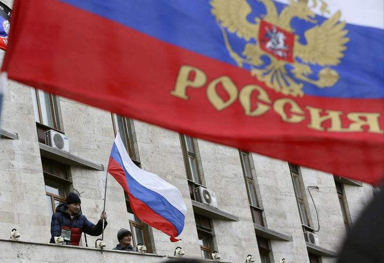 Pro-Russian demonstrators erect a Russian flag outside the regional government building in Donetsk, March 3, 2014. REUTERS/Valeriy Bilokryl