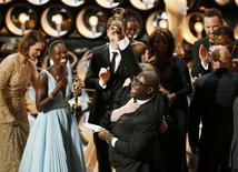 Director and producer Steve McQueen (R) celebrates after accepting the Oscar for best picture with Lupita Nyong'o (L) at the 86th Academy Awards in Hollywood, California March 2, 2014. REUTERS/Lucy Nicholson