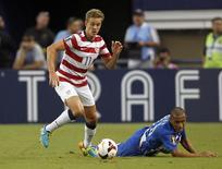 Stuart Holden (L) of the U.S. moves the ball away from Honduras' Alexander Lopez during their CONCACAF Gold Cup soccer match in Arlington, Texas July 24, 2013. REUTERS/Mike Stone