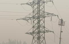 Рабочий чинит ЛЭП у села Криуша в Рязанской области 7 августа 2010 года. Отраслевое энергетическое лобби России заговорило о смягчении тарифной политики в текущем году для российских генерирующих компаний, в то время как профильные ведомства хранят молчание. REUTERS/Denis Sinyakov