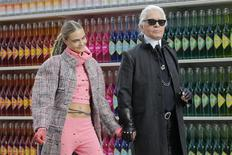 "German designer Karl Lagerfeld (R) and model Cara Delevingne appear at the end of his Fall/Winter 2014-2015 women's ready-to-wear collection show for French fashion house Chanel at the Grand Palais transformed into a ""Chanel Shopping Center"" during Paris Fashion Week March 4, 2014. REUTERS/Stephane Mahe"
