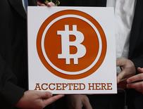 A bitcoin sign is held outside Hong Kong's first bitcoin retail store during its opening, in Hong Kong February 28, 2014. REUTERS/Bobby Yip