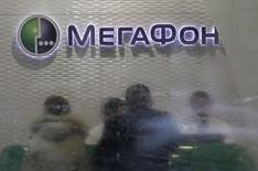 Посетители в магазине Мегафона в Москве 28 ноября 2012 года. Второй по доле рынка телекоммуникационный оператор России Мегафон после отчета за четвертый квартал в среду представил самый оптимистичный прогноз выручки на 2014 год из трех крупнейших мобильных операторов России, ожидая роста этого показателя на 6-8 процентов при стабильной рентабельности на уровне минимум 44 процента. REUTERS/Sergei Karpukhin
