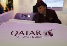 A Qatar Airways flight stewardess shows the airline's new business class seat during the Arabian Travel Market exhibition in Dubai May 6, 2013. REUTERS/Ahmed Jadallah