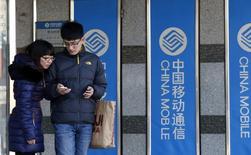 Um homem usa um iPhone da Apple na frente de faixas da China Mobile em uma das filiais da empresa em Pequim. A China vai testar um novo imposto sobre valor agregado para provedoras de serviços de telecomunicações como substituto a um imposto corporativo, disse o premiê Li Keqiang nesta quarta-feira, na abertura da sessão anual do parlamento, em uma mudança que pode afetar os lucros das companhias. 23/12/2013 REUTERS/Kim Kyung-Hoon