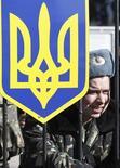 Украинский военный охраняет въезд на территорию подразделения в деревне Любимовка под Симферополем 3 марта 2014 года. Европейский банк реконструкции и развития готов поддержать Украину рассчитанным на шесть лет пакетом помощи, который составит не менее 5-ти миллиардов евро. REUTERS/Vasily Fedosenko