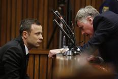 Pistorius fala com um de seus advogados, Brian Webber, no terceiro dia de julgamento em Pretória. O campeão paralímpico sul-africano Oscar Pistorius pediu a um amigo para assumir a culpa por um incidente em que ele disparou acidentalmente uma pistola debaixo da mesa de um restaurante em Johanesburgo em janeiro de 2013, um mês antes da morte de sua namorada, disse uma testemunha durante o julgamento do assassinato da morte da modelo Reeva Steenkamp, nesta quarta-feira. 05/03/2014 REUTERS/MIKE HUTCHINGS