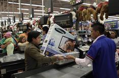Un cliente paga por mercancías al interior de un supermercado de la cadena Wal-Mart en Ciudad de México, nov 17 2011. La confianza del consumidor en México subió en febrero frente al mes previo, cuando tocó su menor nivel en casi cuatro años, impulsada por una mejor percepción de los mexicanos sobre su situación económica actual, dijeron el miércoles el instituto de estadísticas y el banco central. REUTERS/Henry Romero