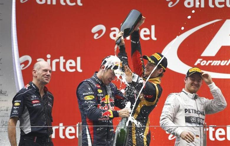 Lotus F1 Formula One driver Romain Grosjean of France (2nd R) sprays Red Bull Formula One driver Sebastian Vettel of Germany (2nd L) after the Indian F1 Grand Prix at the Buddh International Circuit in Greater Noida, on the outskirts of New Delhi, October 27, 2013. REUTERS/Adnan Abidi /Files