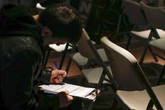 Una persona rellena una aplicación antes de una presentación para trabajos estacionales en Coney Island en Brooklyn, mar 4 2014. Los empleadores privados de Estados Unidos agregaron a sus nóminas a menos trabajadores de lo esperado en febrero y el crecimiento del sector de servicios tocó un mínimo de cuatro años, en las señales más recientes de que el clima severo sigue siendo un lastre para la economía. REUTERS/Shannon Stapleton