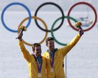 Australia's Mathew Belcher and Malcolm Page pose with their gold medals for the men's 470 sailing class at the London 2012 Olympic Games in Weymouth and Portland, southern England, August 10, 2012. REUTERS/Pascal Lauener